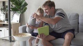 El papá y su pequeña hija están invitando a Skype de una tableta almacen de video