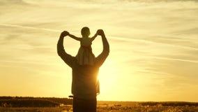 El pap? contin?a hombros de su ni?o querido, en rayos del sol El padre camina con su hija en sus hombros en rayos fotos de archivo