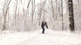 El papá lanza para arriba a su hijo al cielo en parque del invierno almacen de metraje de vídeo