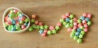 El papel colorido de la estrella de la caja transforma a la forma del corazón en fondo de madera Fotografía de archivo