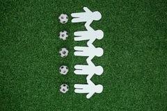 El papel cortó las salidas y los fútboles dispuestos en hierba artificial Foto de archivo