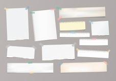 El papel de nota rayado blanco, cuaderno, hoja del cuaderno se pegó con la cinta adhesiva en fondo gris