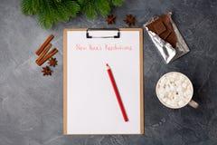 El papel en blanco con las resoluciones del Año Nuevo titula, café, barra del chocolate y lápiz rojo en la tabla gris Endecha pla imagenes de archivo