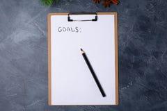 El papel en blanco con metas titula y lápiz negro en la tabla gris Endecha plana Visión superior Concepto del Año Nuevo Espacio l foto de archivo
