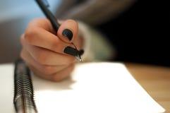 el papel en notas femeninas de la escritura de la mano de la mujer de negocios sobre una tabla ennegrece la manicura y la letra e Fotografía de archivo libre de regalías