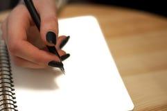 el papel en notas femeninas de la escritura de la mano de la mujer de negocios sobre una tabla ennegrece la manicura y la letra e Imagenes de archivo