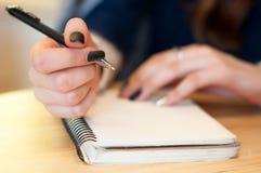 el papel en notas femeninas de la escritura de la mano de la mujer de negocios sobre una tabla ennegrece la manicura y la letra e Fotos de archivo