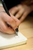 el papel en notas femeninas de la escritura de la mano de la mujer de negocios sobre una tabla ennegrece la manicura y la letra e Foto de archivo libre de regalías