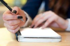 el papel en notas femeninas de la escritura de la mano de la mujer de negocios sobre una tabla ennegrece la manicura y la letra e Imagen de archivo