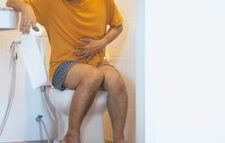 El papel higiénico de la tenencia del hombre y el retrete con con el sufrimiento de la diarrea y los hemorroides despiertan despu imágenes de archivo libres de regalías