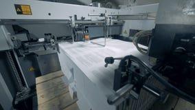 El papel impreso está consiguiendo arrastrado en una máquina industrial almacen de video