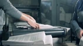 El papel impreso se está quitando del transportador y se está apilando junto almacen de video