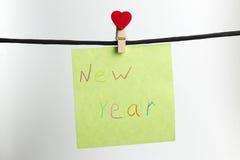 El papel pesa en la cuerda negra con la Feliz Año Nuevo de las palabras Foto de archivo libre de regalías