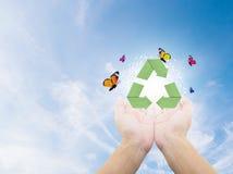 El papel recicla símbolo a mano en la naturaleza Fotos de archivo