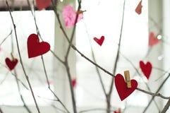 El papel rojo de los corazones cortó con el perno de ropa en ramas de madera Imagen del día de tarjetas del día de San Valentín Foto de archivo