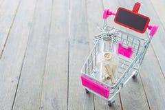 El papel rueda en una botella en un mini carro en la tabla de madera Fotografía de archivo