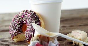 El papel seda inútil, la taza de café y el buñuelo comido mitad del chocolate con asperja almacen de metraje de vídeo