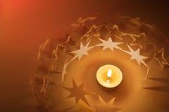 El papel stars el círculo alrededor de luz de la vela Imagenes de archivo