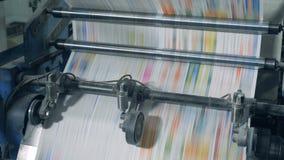 El papel teñido se está moviendo rápidamente a través del mecanismo de impresión Peri?dicos de la impresi?n en tipograf?a metrajes