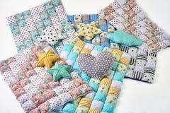 El paquete de consoladores patchworked coloridos con unicornio y las estrellas diseñan y las almohadas en el fondo blanco fotografía de archivo libre de regalías