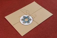 El paquete, letra, embaló en un sobre del vintage con el copo de nieve simbólico Año Nuevo y días de fiesta de la Navidad Fotos de archivo libres de regalías