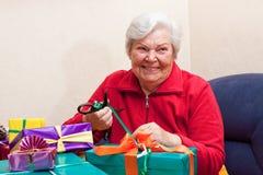El paquete mayor femenino o desempaqueta un regalo Imagen de archivo libre de regalías