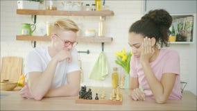 El par étnico multi está comenzando a jugar a ajedrez almacen de metraje de vídeo