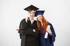 El par abrumado de la universidad gradúa feliz de recibir sus diplomas, sonriendo en la cámara, la muchacha del pelirrojo y el mu Foto de archivo libre de regalías