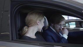 El par acertado alegre que se sienta en el compartimiento de pasajero del nuevo vehículo examina el interior del nuevamente almacen de video