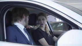 El par acertado de la diversión que se sienta en el compartimiento de pasajero del nuevo vehículo examina el interior del comprad almacen de metraje de vídeo