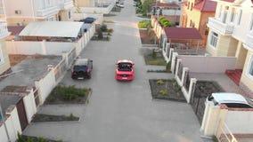 El par acertado en coche deportivo rojo del cabriolé está montando por el pueblo y el parque de la cabaña de la élite cerca del h metrajes