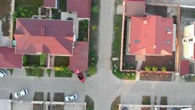 El par acertado en coche deportivo rojo del cabriolé está montando por el pueblo y el parque de la cabaña de la élite cerca del h almacen de metraje de vídeo
