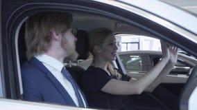 El par acertado feliz que se sienta en el compartimiento de pasajero del nuevo vehículo examina el interior del comprado nuevamen almacen de video