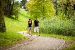 El par adolescente camina en una tarde del verano tardío en parque Fotos de archivo