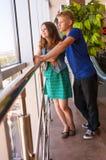 El par adolescente mira en paisaje de la ciudad a través de la ventana Fotos de archivo