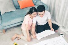El par adulto asiático joven atractivo que mira la casa planea Foto de archivo