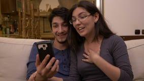 El par afectivo feliz que se sienta en el vídeo del sofá en casa que charla con los amigos parents usando el teléfono elegante almacen de metraje de vídeo
