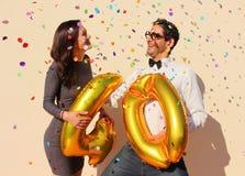 El par alegre celebra un cumpleaños de cuarenta años con los globos de oro grandes y los pequeños trozos de papel coloridos en el Imágenes de archivo libres de regalías