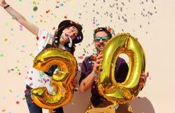 El par alegre celebra un cumpleaños de treinta años imagenes de archivo