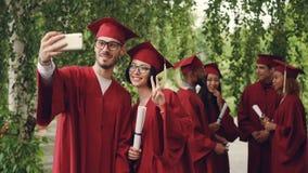 El par alegre de los estudiantes de graduación está tomando el selfie usando el smartphone, hombre joven y la mujer está sostenie metrajes