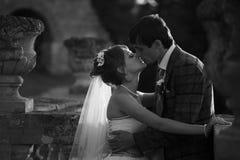 El par apacible se está besando en el medio de los floreros antiguos Fotografía de archivo libre de regalías