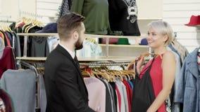 El par atractivo - mujer joven con su marido - elige la ropa en tienda Mujer hermosa que considera el vestido en almacen de video