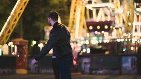 El par bonito atractivo pasa noche de la fecha en el parque de atracciones en la noche