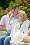 El par bonito se sienta y abrazo en un banco en parque al aire libre Fotos de archivo libres de regalías