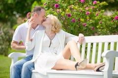 El par bonito se sienta y abrazo en un banco en parque al aire libre Fotos de archivo