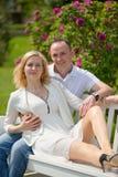 El par bonito se sienta y abrazo en un banco en parque al aire libre Imágenes de archivo libres de regalías