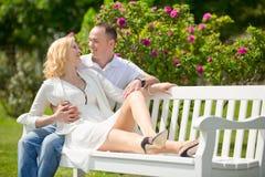 El par bonito se sienta y abrazo en un banco en parque al aire libre Imagen de archivo