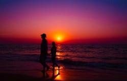 El par camina en la playa con una puesta del sol - imagen común Imagenes de archivo