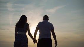 El par camina a lo largo de la costa arenosa en la puesta del sol metrajes