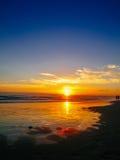 El par camina a lo largo de la playa en la puesta del sol foto de archivo